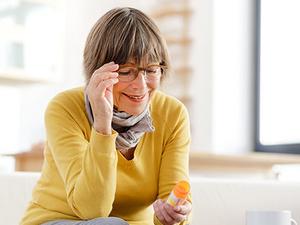 Eine ältere Dame mit Brille sitzt auf dem Sofa und liest die Aufschrift auf einer Arzneimittelpackung.