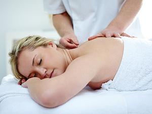 Ein Akupunkteur behandelt eine Dame mit seinen Akupunkturnadeln. Sie liegt auf der Behandlungsliege.