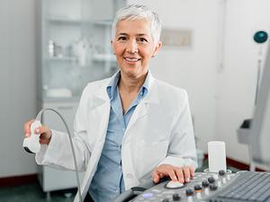 Eine Ärztin mit grauen Haaren sitzt im Behandlungszimmer und bedient ein Ultraschallgerät.