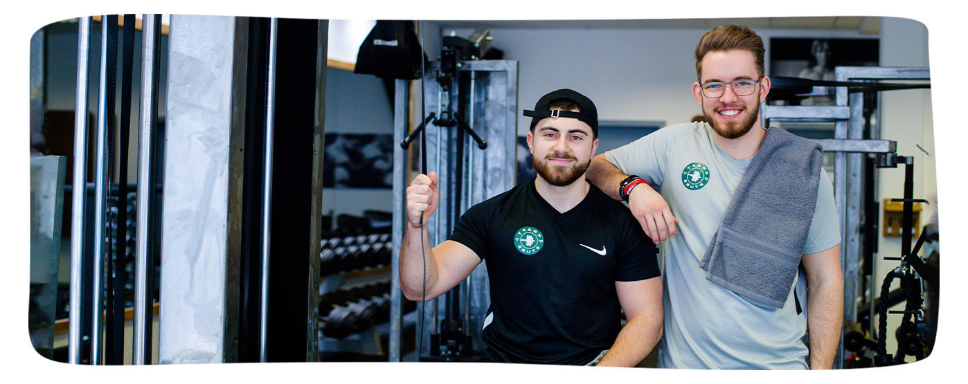 Trainingspartner im Fitnessstudio lachen in die Kamera