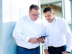 Zwei Herren schauen in einen Tablet-PC