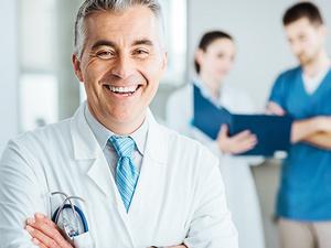 Ein Arzt mit einem weißen Kittel lächelt mit verschränkten Armen in die Kamera.