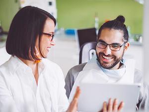 Eine Zahnärztin schaut gemeinsam mit einem männlichen Patient in seine Patientenunterlagen.