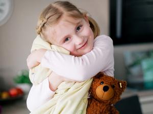 Junges Mädchen kuschelt mit ihrem Teddy und Kissen