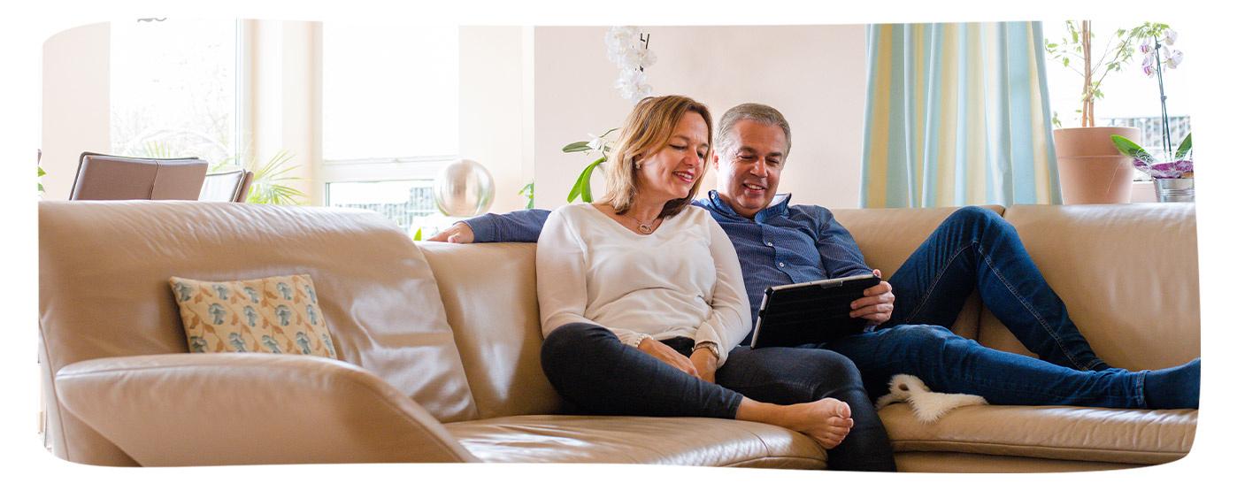 Unsere Versicherten Susanne und Michael Reitz aus Meinhard nutzen ihr Tablet im Wohnzimmer