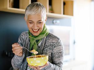 Ein Dame mit kurzen gräulichen Haaren steht in der Küche und isst Müsli aus einer Schale.