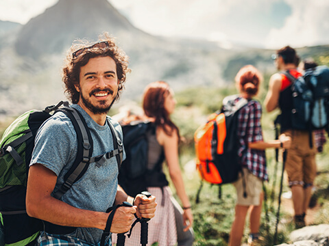 Ein Mann mit längerem Haar lächelt in die Kamera, während er mit seinen Freunden auf einen Berg hinauf wandert.