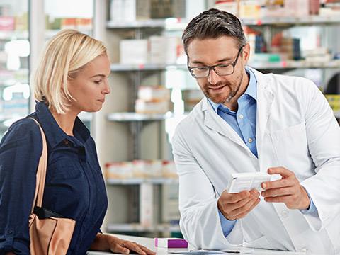 Eine junge blonde Dame wird in der Apotheke von einem Apotheker mit Brille beraten. Sie schauen sich gemeinsam ein Medikament an.