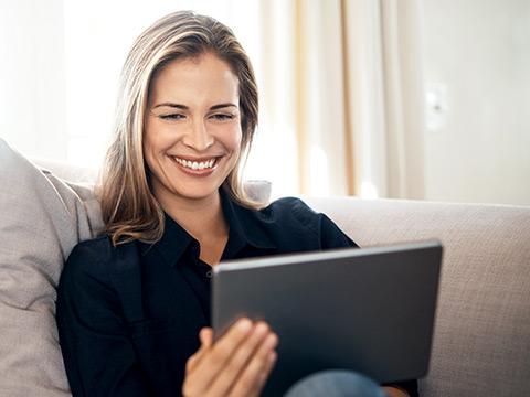 Eine Frau sitzt auf der Couch und sieht sich etwas auf einem Tablet-Computer an. Sie lächelt dabei.