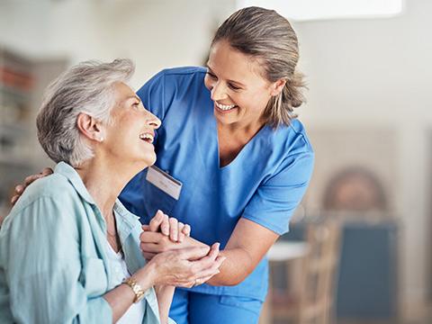 Eine ältere Frau im Pflegeheim wird von einer weiblichen Pflegekraft betreut.