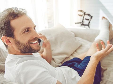 Ein junger Mann liegt daheim auf der Couch mit einem gebrochenen Bein. Er telefoniert mit seinem Handy.