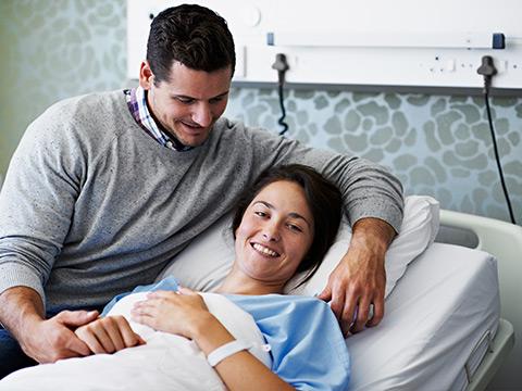 Eine junge Dame liegt im Krankenhausbett. Ihr Mann besucht sie und hält ihre Hand.