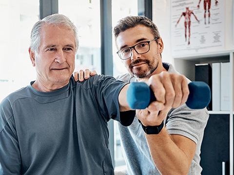 Ein Physiotherapeut leitet einen älteren Mann beim Krafttraining an. Er streckt den Arm aus und hebt einen Hantel.