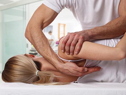 Ein Therapeut behandelt eine junge Dame durch gezielte Griffe an der Schulter.