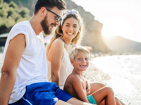Ein kleiner blonder Junge sitzt gemeinsam mit seinen Eltern an der Strandpromenade während des Sonnenuntergangs.