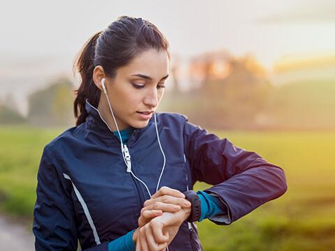 Eine dunkelhaarige Frau joggt bei Sonnenaufgang und schaut dabei auf ihre Uhr.