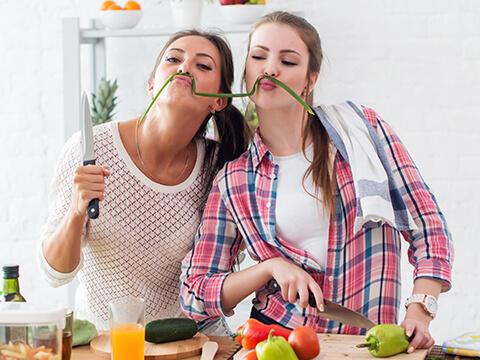 Zwei junge Frauen schneiden in der Küche gemeinsam Gemüse und haben sich mit einem Stück Lauch einen Schnurrbart gebastelt.