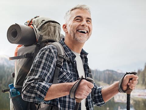 Ein grauhaariger Mann lacht glücklich während mit einem Rucksack ausgestattet einen Berg hinauf wandert.