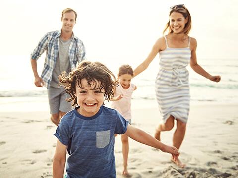 Eine vierköpfige Familie läuft gemeinsam am Strand entlang und sie haben dabei viel Spaß.