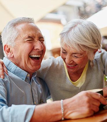 Zwei Senioren sitzen gemeinsam am Tisch und halten sich im Arm. Sie lachen sehr herzhaft zusammen.