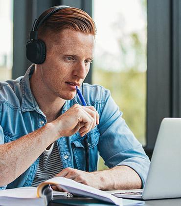 Ein junger männlicher Student sitzt am Schreibtisch und arbeitet an einer Hausarbeit, die er mit seinem Laptop schreibt. Er hält einen Stift in der Hand und denkt nach.
