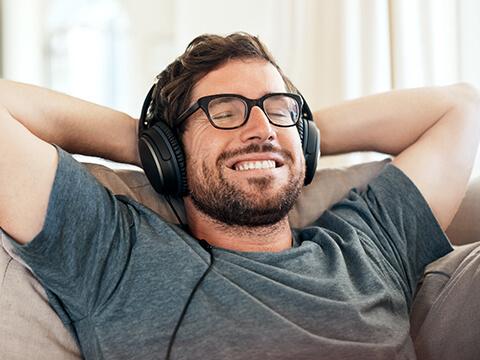 Ein Mann sitzt mit geschlossenen Augen auf der Couch hört mit Kopfhörern Musik.