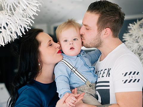 Eine junge Mutter und ein junger Vater halten ihr Kind in ihrer Mitte und küssen den kleinen Jungen auf die Wange.