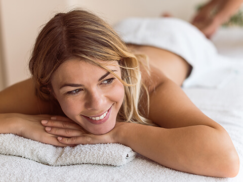 Eine junge blonde Dame liegt auf einer Massageliege und entspannt.