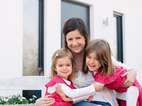 Eine Versicherte der BKK Werra-Meissner hat ihre zwei Töchter im Arm, während alle drei in die Kamera lachen.
