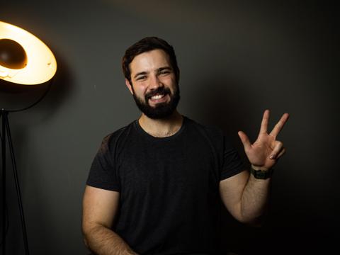 Junger Mann mit Bart hält drei Finger hoch und lacht in die Kamera.