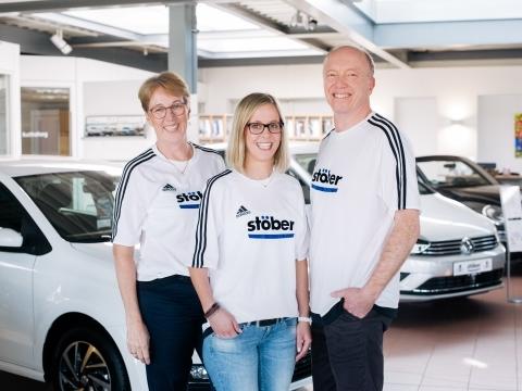 Mitarbeiter des Autohauses Stöber lächeln im Autohaus in die Kamera